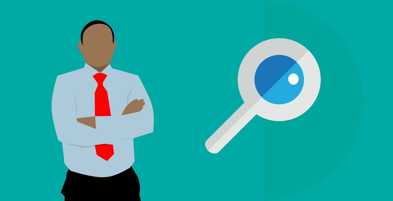 Image of a Professionally suited person and a magnifying glass